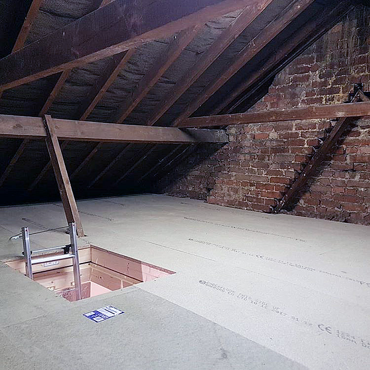 Loft insulation and exposed wooden beams with floor boarding