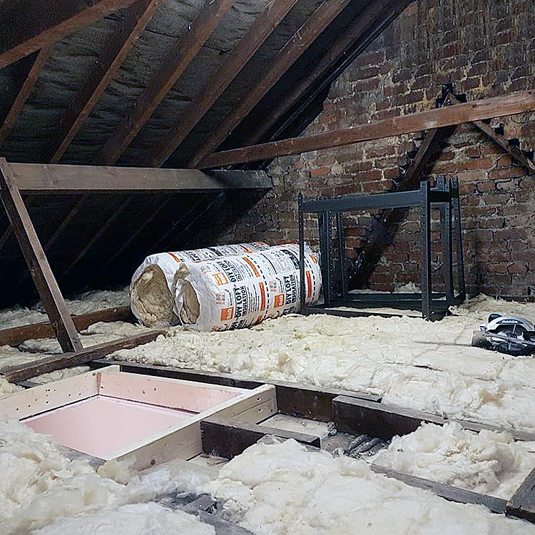 Loft insulation and exposed wooden beams and rolls of insulation without floor boarding