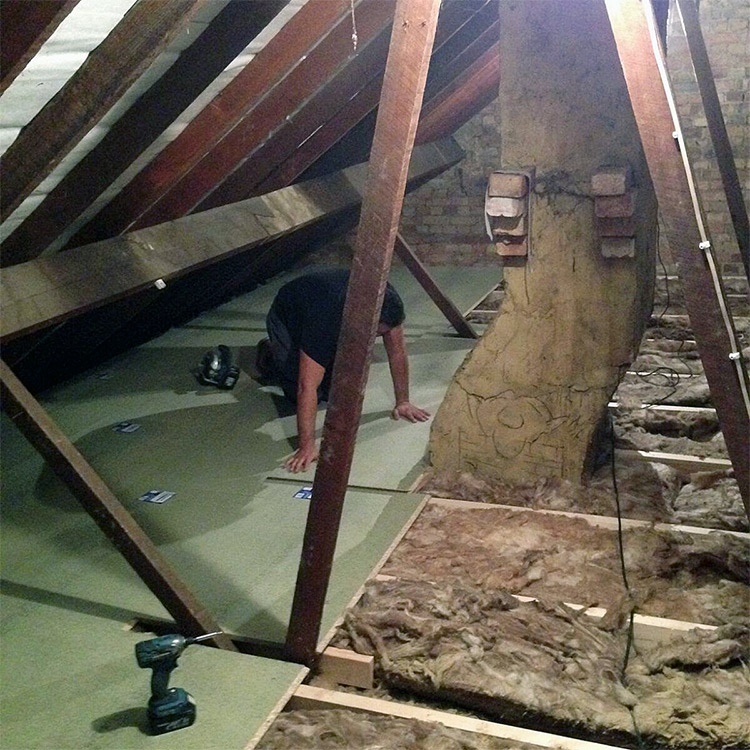 Person fitting Loft boarding over loft insulation