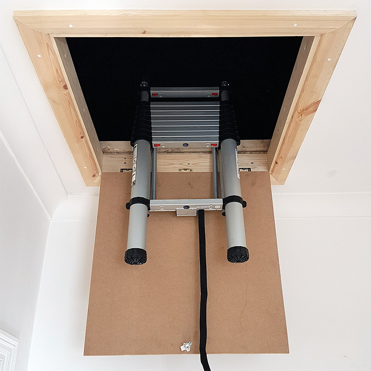 Stored telescopic loft ladder above loft hatch
